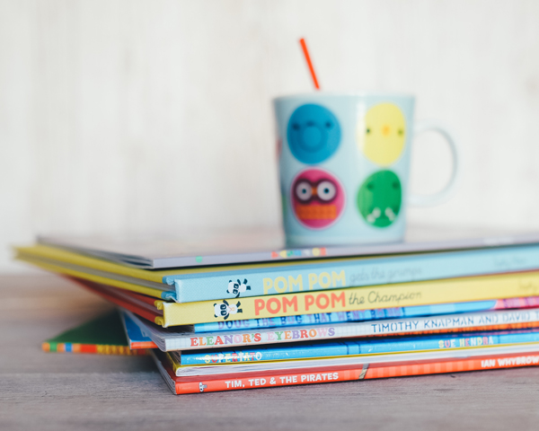 children's cup on top of preschool books