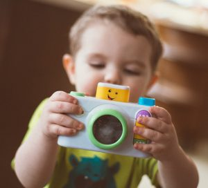 toddler playing with toy camera in Wetherill Park preschool centre